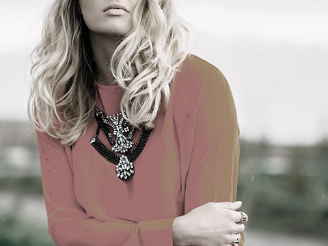 Prestation luxe, jeune femme portant un sweat shirt orange exhibant son collier et ses bagues.